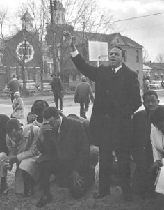 Praying/Preaching a sermon of freedom on a cold winter day. From left, John Lewis of SNCC (kneeling), Hosea Williams of SCLC (kneeling), and Andy Young of SCLC (standing). Movement headquarters Brown Chapel is in the background.