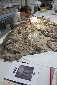 """Anne Getts, UD graduate student in the Winterthur-University of Delaware Program in Art Conservation, helps restore the gown which was designed by Gilbert Adrian and worn by leading lady Norma Shearer in the 1938 MGM movie """"Marie Antoinette."""