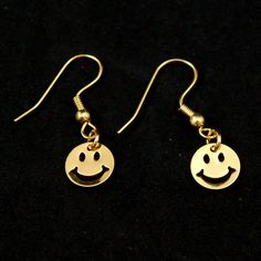 Golden Smiles Earrings:Happiness is...these little golden smile earrings! These darling gold dangle earrings measure .25 inches and are on a gold hook. These are vintage dead stock and have never been worn. $4.00