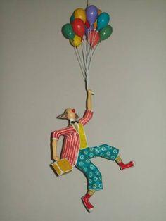 Escultura em papel e arame, para pendurar, de um palhaço voando com balões. R$200,00