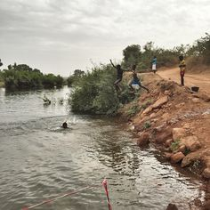 Two girls jump into a branch of The Gambia River near Afia village in southeastern Senegal. Women on the other bank were washing laundry. (Ricci Shryock - photographer | video journalist)