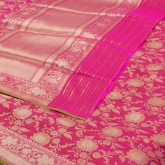 """This """"Razzmatazz Pink"""" colour #Handwoven Banarasi Katan Silk Sari is woven with zari creeper floral motifs all over the body and bordered on either side by zig-zag gold colour zari floral motifs. The """"Razzmatazz Pink"""" colour pallu is adorned with bands of gold colour zari. The border is repeated on """"Chestnut Rose"""" with zig-zag floral motifs blouse completes the sari."""