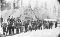 Several dozen lumbermen pose in front of the large main building at a logging camp near Cadillac, c. 1896