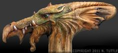 ''Dragon Time'' by Nancy Tuttle -- ''Another fun carving! This was a nice solid piece of wood that allowed me to easily create the details of this Dragon's face. His teeth were modeled after an alligator, his eyes from a snake and his skin from a lizard. The rest is pure imagination. Everything has been carved into a single piece of Oregon driftwood. I used oil paints to add color to his face and his eye.''