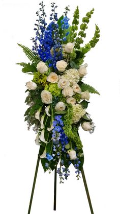 Elegant blue, white and green hydrangeas, roses, mini callas, delphinium, bells of Ireland standing spray.  Blue, white and green flowers are a favorite of our clients for sympathy arrangements.  This one is over 7' tall on a 5.5' stand. #sympathyflowers #funeralflowers #florist