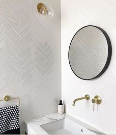 White Herringbone tiled walls, brushed brass wall spout and mixer set, brushed brass towel holder, rectangular undermount basin with overflow in white Carrara marble top vanity finished off with a matte black framed round mirror. Bad Inspiration, Bathroom Inspiration, White Herringbone Tile, Chevrons, Budget Bathroom, Bathroom Beach, Mirror Bathroom, White Bathroom, Small Bathroom