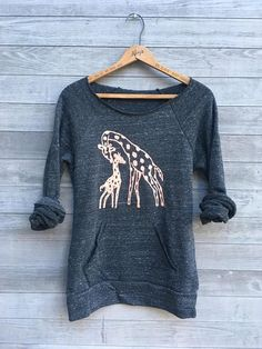 Me and Mama Giraffe this sweatshirt is COMFY + COZY + WARM. This top has a scoop neck and ultra soft fleece interior. runs a bit wider but shorter than my off shoulder tops and there is no pocket. A Baby and Mama Giraffe are printed in light orange. GIFT WRAP OPTION- available in