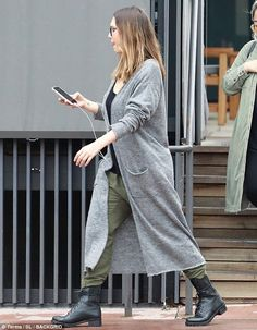 Keeping casual: The mother of three styled her rainy day attire with a black T-shirt, addi...