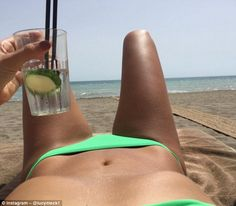 Cheers: On Sunday Lucy uploaded a sexy snap of her enviably flat stomach as she soaked in the sun at Laguna Beach