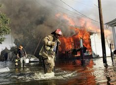 A New Orleans fireman helps evacuate a man out of flood waters as a home burns in the seventh ward of New Orleans during the aftermath of Hurricane Katrina August 6, 2005.   Photo credit: REUTERS/Shannon Stapleton