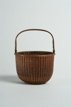 """Nantucket Light Ship Basket with Swing Handle Nantucket, Massachusetts, first half 20th century Ink inscription on the bottom: """"BARTEL"""" H. (with handle) 6 _ in.; Diam. 5 in.  Estimate: $400 - $800  Condition: There is minor loss of one splint.  Price Realized: $2,108"""