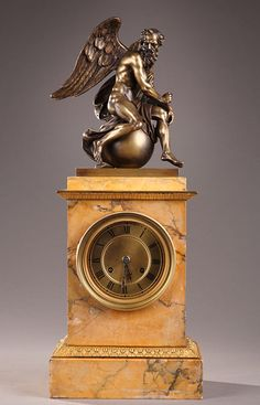 A gilt and patinated bronze clock representing a winged Chronos overhanging the mecanism mounted inside of the Sienna marble rectangular-based body of the clock.
