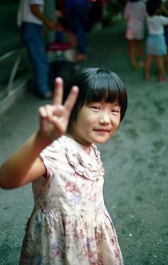 Peace Offering from a Little Part of Okinawa  A young girl gives me the peace sign as I ask her for a photo. I shot this during an Eisa festival in Kin Cho city, in Okinawa. by Tim.
