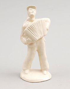White glazed sculpture of a accordion player design Etha Lempke ca.1935 executed by Plateelbakkerij Zuid-Holland Gouda / the Netherlands