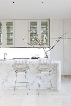 White kitchen cabinets -love. hardware? carrera marble waterfall island. Bertoia barstools