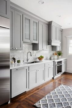 Shaker style kitchen cabinet painted in Benjamin Moore 1475 Graystone. The walls are Benjamin Moore Dove Wing.  The tile on the backsplash is from Ann Sacks and it is part of a Barbara Barry collection they carry.