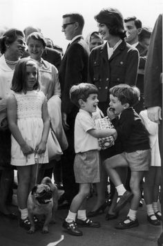 Jacqueline Bouvier Kennedy (right) stands with her daughter, Caroline, her son, John F. Kennedy Jr. (center), and her nephew, Anthony Radziwill. Caroline holds her pet pug on a leash.