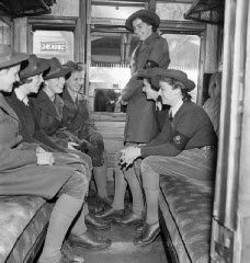 Land Army girls looking very smart in their new uniforms as they travel to their posting by train. WWII