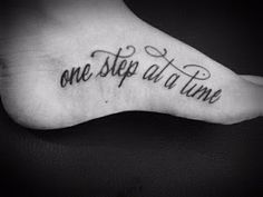 One step at a time quote tattoo on side foot