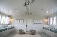 Chic boy's room with beadboard cathedral ceiling, chair rail & wainscoting & white built-in daybeds with storage