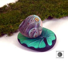 Two hand painted river stones, a toad sitting on a lily pad.  Measures : leaf 10 cm., toad 6 x 5 cm.  weight : leaf 230 grams + toad 120 grams =