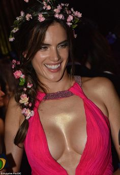 Alessandra Ambrosio sports VERY plunging pink dress slit to the thigh at Vogue party  It looked like she had spent a long time at the hairdresser, weaving a pretty chain of pink flowers into her long brown braid.  But it was doubtful that many partygoers would have paid too much attention to Alessandra Ambrosio's striking headdress at the Vogue Carnival party on Thursday night.