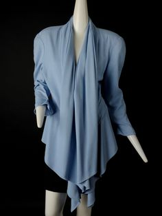 Fantastic late 1980s suit jacket in a sky blue rayon gabardine. The jacket has built up shoulders and a pleated, draped collar and lapels that extend down the front and ending in points. The jacket ha