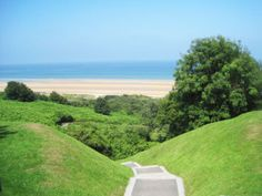 Omaha Beach seen from Colleville-sur-Mer American War Cemetery, the craters from the artillery still exist today. The land has been left untouched.