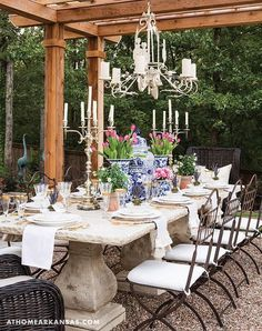 Whimsical garden features a French style concrete dining table seating eight wrought iron dining chairs with white cushions and two wicker host chairs illuminated by a chandelier hung from a pergola.
