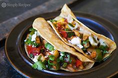 Veggie Tacos ~ Vegetarian tacos with onions, zucchini, tomatoes, green chiles, jalapeños, cheddar and cotija cheeses, and cilantro in corn tortillas. ~ SimplyRecipes.com