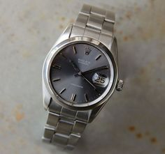 "This is a Rolex oysterdate from 1974. Grey dial Ref. 6694. Manual movement. The high-grade calibre 1225 movement is complete with 17 rubies. 34mm diameter. Brushed and polished case with plain bezel, screw down Rolex oyster crown and screw on back. 8"" Rolex Oyster bracelet ref.78350. The piece is in original condition and keeps very good time. We have fully serviced and regulated the movement."