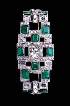 A DIAMOND AND EMERALD BROOCH  Designed as a rectangular-cut diamond and emerald openwork geometric panel with central old European-cut diamond to the diamond line spacers and calibré-cut emerald terminals, circa 1928