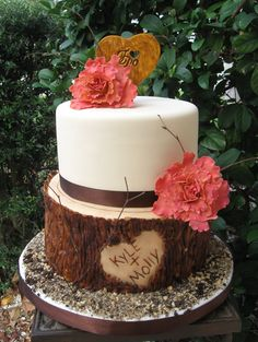 """8"""" and 10 inch vanilla cake with strawberry filling. The bottom is covered with chocolate marshmallow fondant in many colors and then painted. The top is also fondant. Flowers and """"I do"""" sign gumpaste with vanilla and chocolate cookie crumble around the bottom.."""