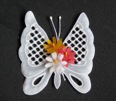 Borboleta em papel vegetal, confeccionada em tela, centro com flores ou cristais. Dimensões aproximadas: 8x10 cm. Pedido mínimo: 20 unidades. R$ 10,00
