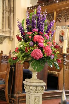 At the Aisle end just before the altar two dramatic pedestals of deep purple English Delphiniums, Agapanthus, Larkspur, Scabious, Stocks, Dahlias and Hydrangeas were placed to frame the Ceremony