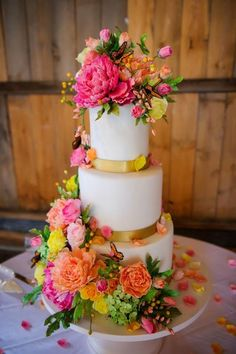 Colorful sugar flowers and sugar butterflies flow over this wedding cake by The Mischief Maker.