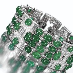 CABOCHON EMERALD AND DIAMOND BRACELET, VAN CLEEF & ARPELS, CIRCA 1935. The wide strap set with 50 oval cabochon emeralds arranged in three flexible segments joined by rectangular links and completed by a buckle clasp, set with numerous round, single-cut  and baguette diamonds weighing approximately 25.00 carats, mounted in platinum, length 7 inches, signed Van Cleef & Arpels, numbered 33175.