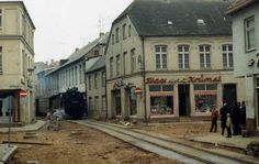 Molli with Flax und Krümel , Bad Doberan DDR Jan 1990   Road surfacing outside the elegantly lettered Flax und Krümel shop as a train bound for Kuhlungsborn squeezes between the houses. Flax und Krümel was the very first TV series in the GDR solely for children, running from 1955 until 1970, utiliing puppets. I guess this was a toyshop. Locomotive no 99 2323-4