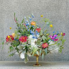 Remember this beauty? Well, we're still shamelessly in love  #ThinkFlowers | From @mccarthyflorists Instagram | Photo includes our boho-inspired wedding centerpiece of dahlias, ranunculus, delphinium, anemones, billy balls, hydrangea, rustic greens such as eucalyptus, dusty miller and veronica. | Photo belongs to McCarthy Group Florists.