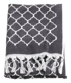 Bath towel in cotton terry with a jacquard-weave pattern, fringe along short sides, and hanger loop on one long side.