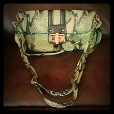 Purse Very vibrant faux snake skin green handbag. Bamboo wooden toggle closure. One adjustable shoulder strap that could make it a crossbody fit. Another strap that's perfect for the shoulder. Or take them both off for a unique clutch. Three inside pockets. Flap has two magnets, one in each corner, for extra support when closed. Also comes with a protective dust cover. A great conversation piece. Mellow World Bags Shoulder Bags