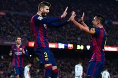 Gerard Pique of FC Barcelona celebrates with his teammate Xavi Hernandez of FC Barcelona after scoring his team's third goal during the La Liga match between FC Barcelona and Cordoba CF at Camp Nou on December 20, 2014 in Barcelona, Catalonia.