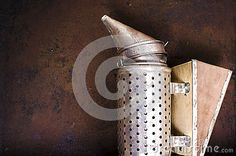 Vintage beekeeping smoker on rusty background