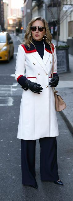 white long wool military coat with gold double-breasted buttons and navy and red accent collar and cuffs, navy wide leg pants, classic patent leather pointy toe pumps, cashmere turtleneck