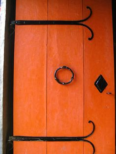 A bright orange door punctuated with glossy black hardware