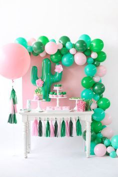 Pink and green cactus birthday party dessert table inspiration. Balloon wall garland. Cactus balloon with tissue paper flowers. Matching tissue paper tassel garland. Cactus Party styling by Happy Wish Company. Photography by Tammy Hughes Photography. Stationery by Minted artist, Baumbirdy.