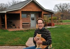 Jeff Harshbarger holds one of the couple's cats, Yogi, who lives in the cat house Jeff built, in the background.