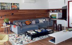 O painel de madeira cumaru cobre uma parte da parede. Sobre ele, ficam apoiados os quadros. Na prateleira do canto, há mais exemplos. Projeto de Andrea Reis