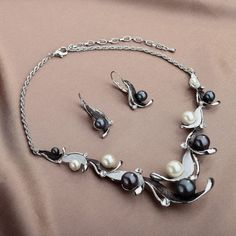 $12.95  This necklace earrings jewelry set features colorful metal wavy leaf motifs adorned with same color pearls and rhinestones. Crafted in silver tone alloy, the Leaf Pearl Necklace suspends from a rope chain. The matching pearl earring is designed in same style with lever back ear wire.