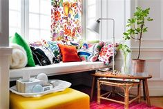 sweet, colorful mix of throw cushions on a window seat